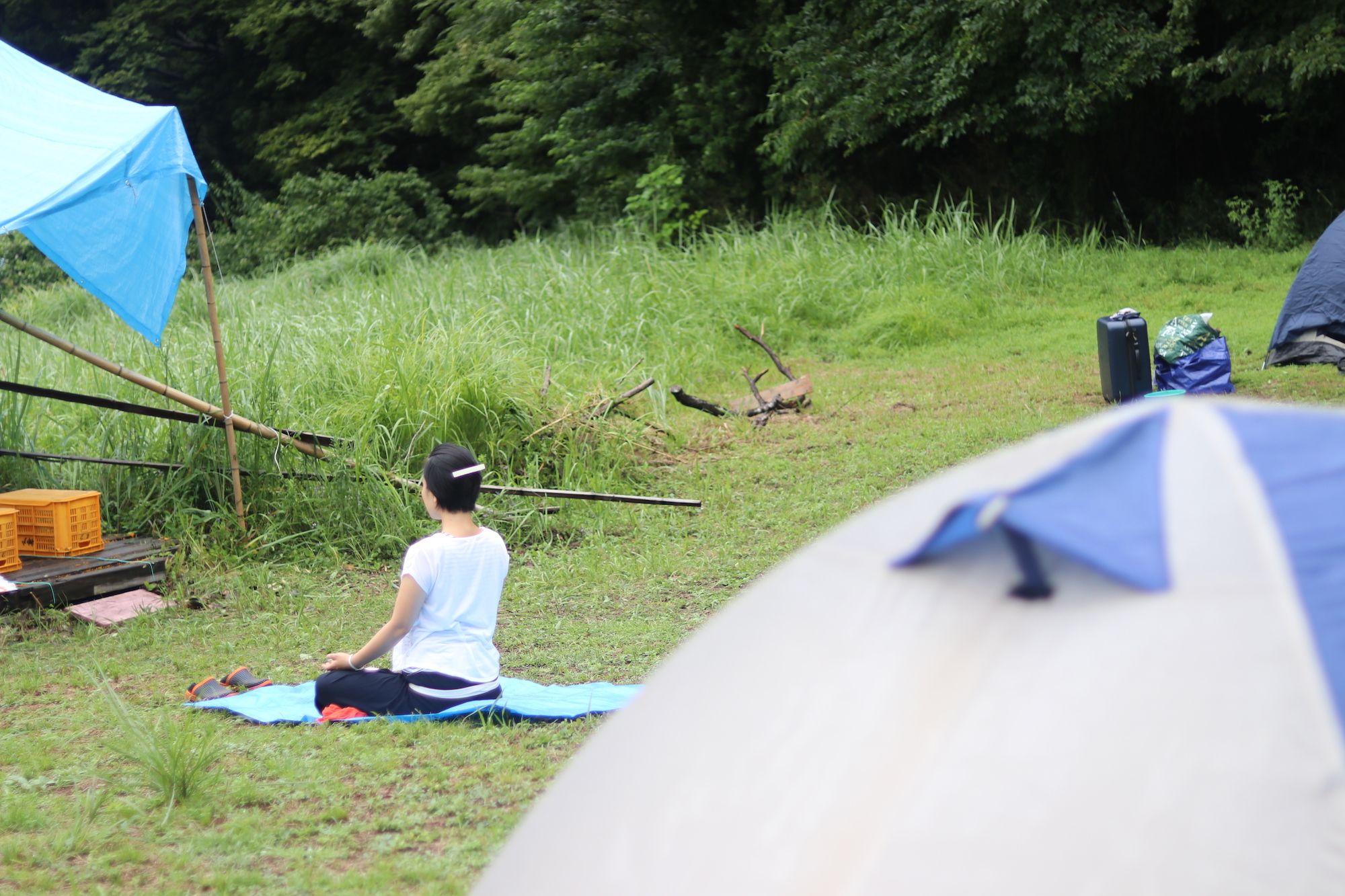 朝、谷側を向いて一人静かに瞑想する女性。